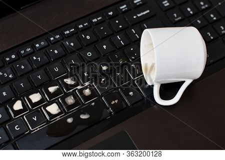 Spill Coffee From White Cup On The Computer Laptop Keyboard.damage To Computer Due To Spilled Liquid