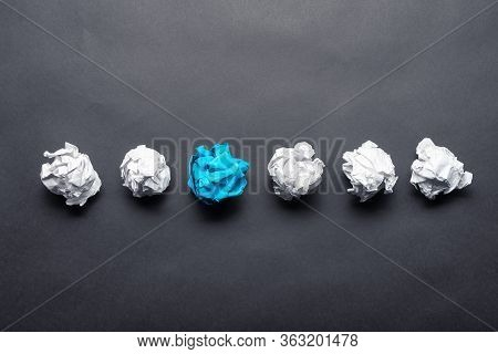 Crumpled Blue Paper Ball Among White Balls On Black Background. Extraordinary Solution Of Problem. T