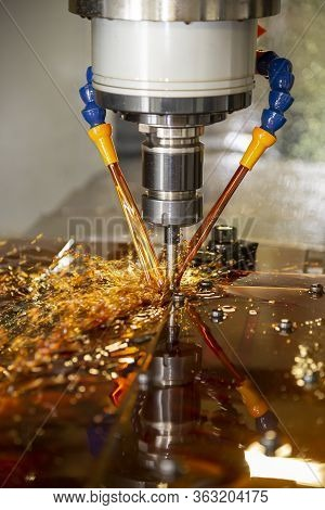 The Vertical Scene Of Cnc Milling Machine  Cutting The Mold And Die Parts With Liquid Coolant Method