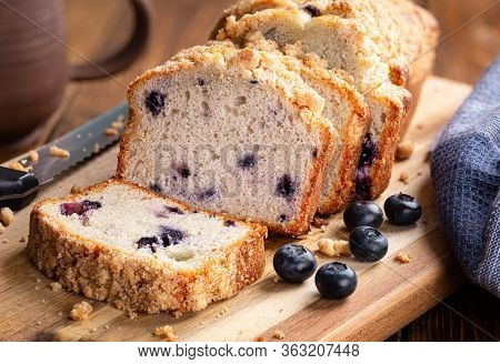 Closeup Of Sliced Blueberry Streusel Loaf Bread And Fresh Berries On A Wooden Cutting Board