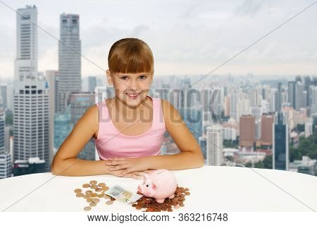 Little Lovely Girl With Coins And Piggy Bank On The Desk Over City Background. Saving Money For Educ