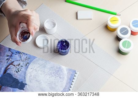 A Female Hand Holds A Lid From A Jar On Which Paint Is Mixed Against The Background Of A Cat On A Tr