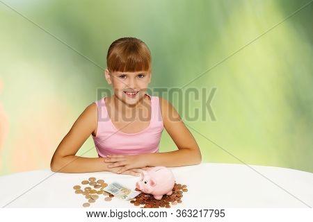 Little Lovely Girl With Coinsand Pig Bank On The Desk Over Green Background. Saving Money For Educat