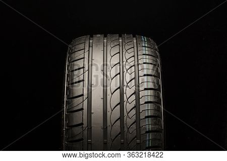 Asymmetric Summer Tire. Front View, Close-up On A Black Background