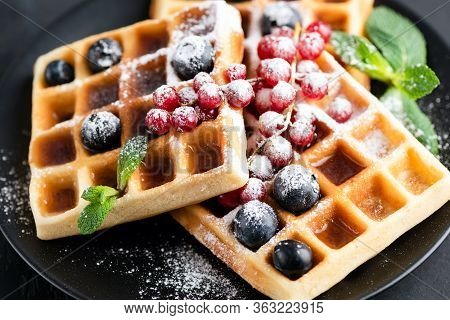 Square Belgian Waffles With Berries And Icing Sugar On A Black Plate. Tasty Sweet Sugary Waffles