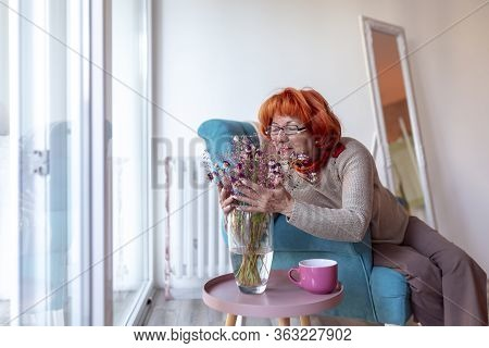 Senior Woman Sitting In An Armchair, Arranging A Flower Bouquet Into A Vase And Relaxing At Home