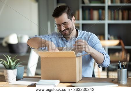 Smiling Man Unpacking Awaited Parcel, Sitting At Work Desk