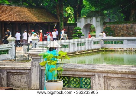 Vietnam Woman Wearing A Straw Hat And Wear  Blue Dress Ao Dai Standing Beside The Pond In Tourist At