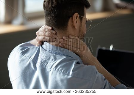 Close Up Tired Young Man Massaging Stiff Neck Muscles