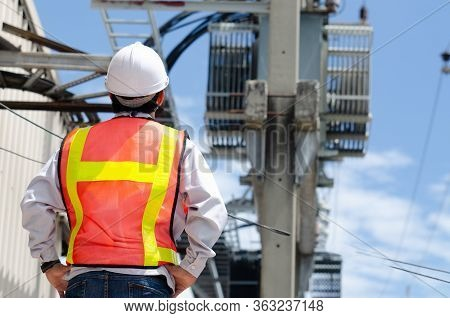 Electrical Engineers Standing At The Job Site With A Transformer Background On An Electric Pole