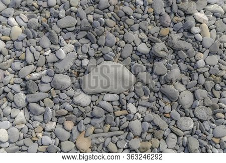 Grey Beach Pebbles With One Large Pebble In The Center