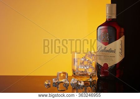 St.Petersburg, Russia - February 2020 - Bottle of Ballantine's Finest blended scotch whisky and glass with ice on mirror surface on yellow background with copy space. Product of Scotland