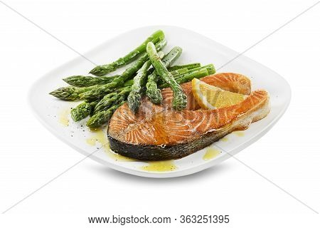 Fresh Boiled Asparagus And Baked Salmon Steak With Dressing Sauce On Plate
