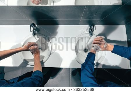 Top View . Colleagues Wash Their Hands In The Office Restroom