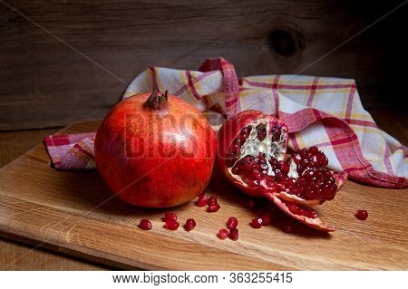 Fresh Red Pomegranate On A Wooden Background..