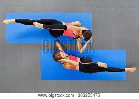 Top View Of Two Young Active Women With Slim Body Doing Bicycle Abdominal Crunches Exercise On Yoga