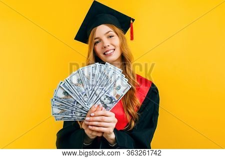 Beautiful Graduate Girl, In A Black Gown, And A Black Master's Hat, With Dollars In Her Hands, Marks