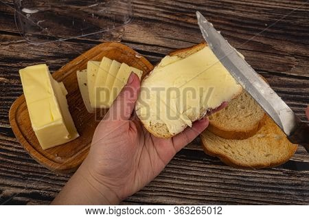 Someone Spreads A Little Butter With A Knife On Fresh Wheat Toast, A Piece Of Butter In A Wooden But