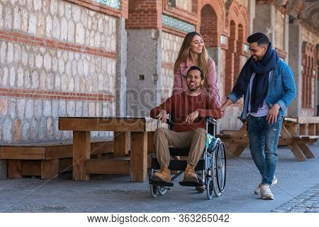 A Young Paralyzed Latino Boy In A Wheelchair Accompanied By A Young Latin American And A Caucasian G