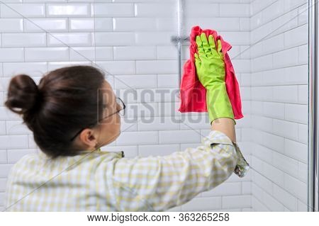 Woman Doing Cleaning In The Bathroom, At Home. Female Cleaning Polishing Shower Glass With A Washclo
