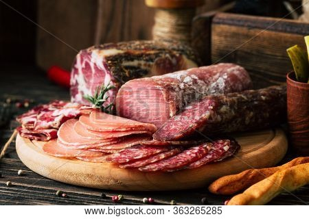 Meat Delicacies On Wooden Background, Dried Sausage On A Cutting Board