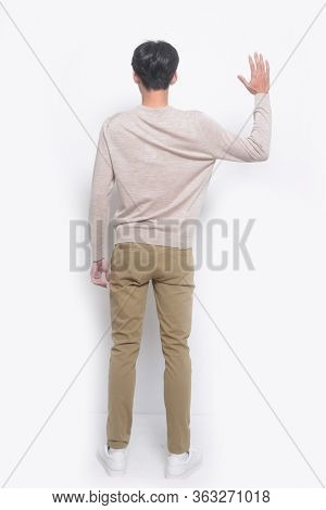 full length handsome casual man wearing sweater with khaki pants standing doing stop sing with palm of the hand.on white background,back view