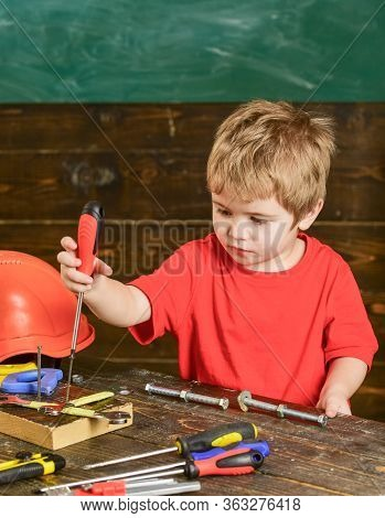 Little Repairman In Workshop. Boy Binding Screws To Wooden Board. Kid Playing With Instruments