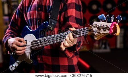 Male Hands Holds Bass Guitar, Play Music In Club Atmosphere Background. Play Guitar Concept. Musicia