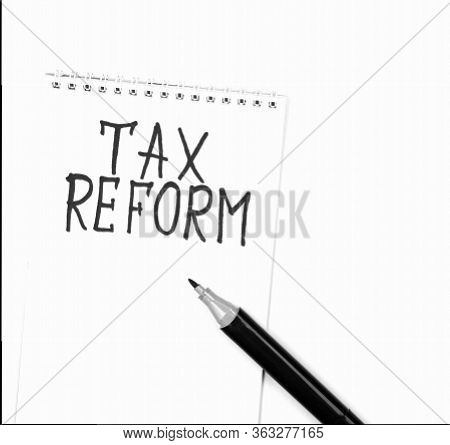 Black Marker Writing The Words Tax Reform On A White Notepad. A Concept Calling For Early Implementa