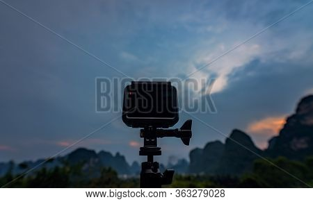 Small Portable Action Camera On A Tripod Recording Time-lapse Video Of A Sunset Over Beautiful Impre