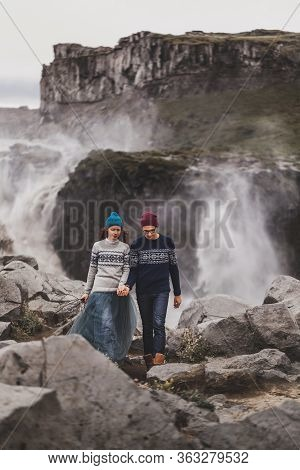 Young Stylish Couple In Love Walking Together Near Famous Icelandic Dettifoss Waterfall. Traditional
