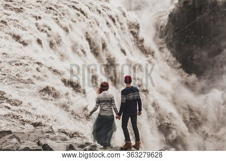 Young Couple In Love Looking At Famous Icelandic Landmark Dettifoss Waterfall. Traditional Wool Swea
