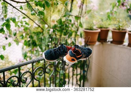 Washing And Drying Sneakers. The Crumbs Are Dry On The Balcony. Drying Shoes In A Natural Way. A Pai