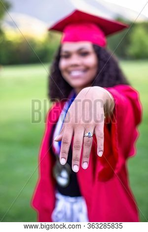 Multiethnic woman in her graduation cap and gown showing her class ring. Selective focus on the hand and ring. Way to go. Great Job Graduate!
