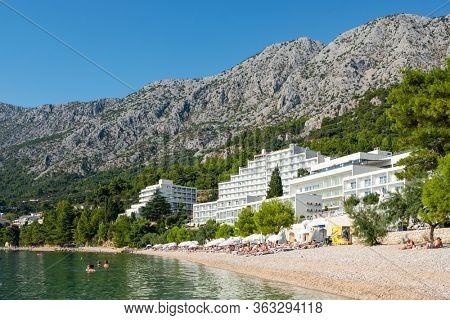 Makarska, Croatia - September 4, 2019: Unidentified people rest at the beautiful beach at Adriatic Sea in Makarska Riviera, Dalmatia, Croatia