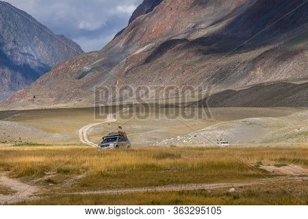 Altai, Mongolia - June 14, 2017: Cars With German And Mongolian Flags On Winding Road In The Altai M
