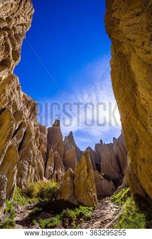 Colossal clay peaked outliers - Clay Cliffs in the hills separated by narrow ravines. New Zealand. Sunset. The concept of exotic, extreme, natural and photo tourism