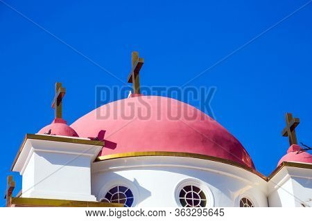 The Jerusalem Orthodox Church. Snow-white church building with pink domes and golden crosses. Place of worship and pilgrimage. Israel. Capernaum. The concept of religious pilgrimage