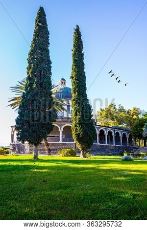 Flock of migratory birds flies. High shore of Lake Tiberias. The Catholic Church of the Italian female Franciscan monastery on Mount Bliss in the Galilee. Israel. The concept of   photo tourism