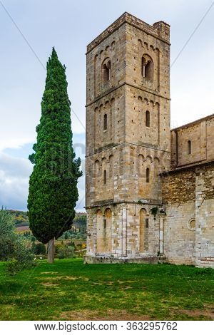 Picturesque Tuscany. Ancient medieval magnificent abbey of San Antimo. Tall slender cypress adorns the meadow around the abbey. The concept of active, rural and photo tourism
