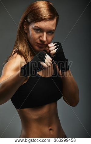 Female Boxer With Hands In Black Boxer Bandages In A Boxer Stance On A Dark Gray Background, Posing
