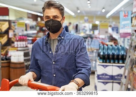 Casual middle aged man in face mask shopping in grocery store supermarket.