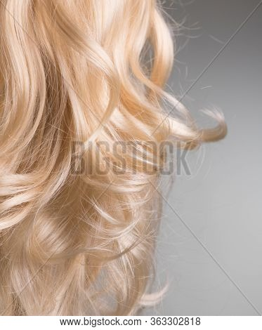 Blond Hair. Beautiful healthy long curly blonde hair close-up texture. Dyed Wavy white hair background, coloring, extensions, cure, treatment concept. Haircare.