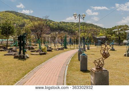Jinan, South Korea; April 21, 2020: Brick Walkway Through Park Of Welded Iron Sculptures At Yongdam