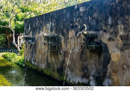 Water Flowing Out Of The Three Ornamental Fountains Mounted On The Wall In The Tropical Landscaped F
