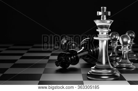 King Of Clear White Chess Has Made Checkmate King Of Black Chess In Dark Black Background. Concept O
