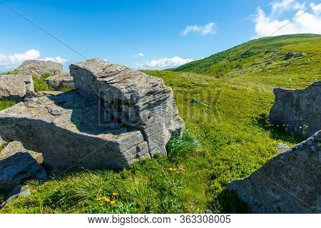 Rocks On The Alpine Hillside Meadow. Beautiful Summer Nature Landscape. Green Grass On The Hills And
