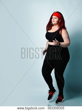 Calm Concentrated Plus-size Girl Does Exercises Jogging Slowly In Place On Light Blue Background. Fi
