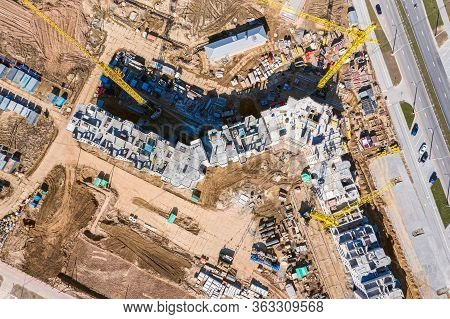 Aerial Top View Of Construction Site With Multi-storey Residential Building And Yellow Cranes