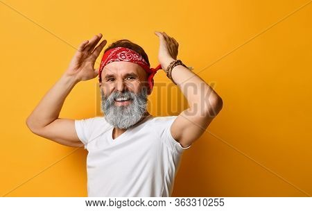 Gray-bearded, Brunet, Aged Male In Red Bandana, White T-shirt And Bracelet. He Put His Hands On Head